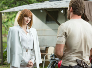 A clad-in-all-white character approaches a man with a trailer who specializes in raptor knowledge...sound familiar?